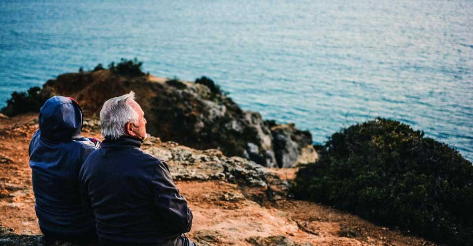 Older people sitting together in front of the sea Photo by katarzynagrabowska - Unsplash